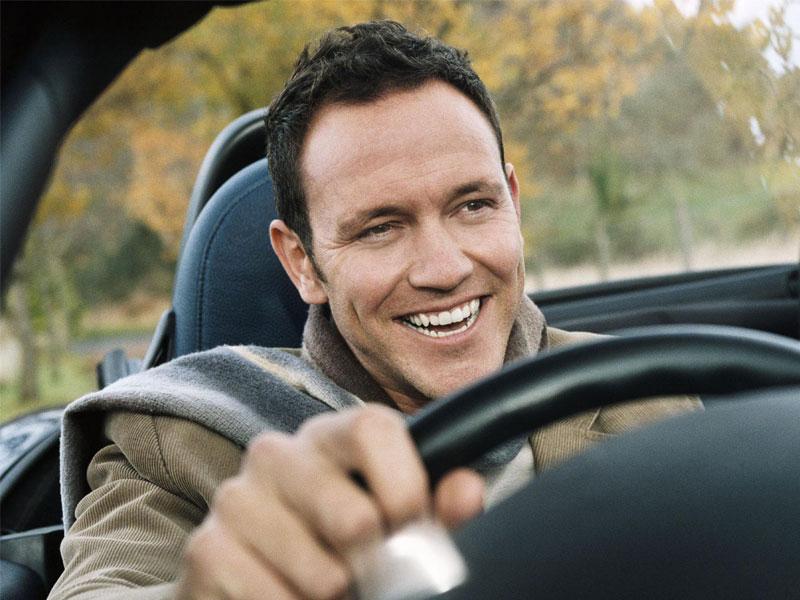 Счастливый водитель за рулём автомобиля